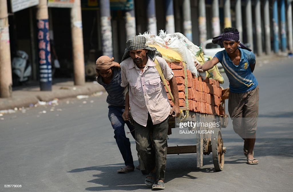 Indian labourers push a handcart loaded with bricks along a street in the old quarters of New Delhi on May 1, 2016. / AFP / SAJJAD