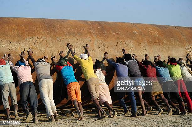 TOPSHOT Indian labourers push a pontoon to construct a temporary pontoon bridge over the River Ganges for the upcoming Magh Mela festival in...
