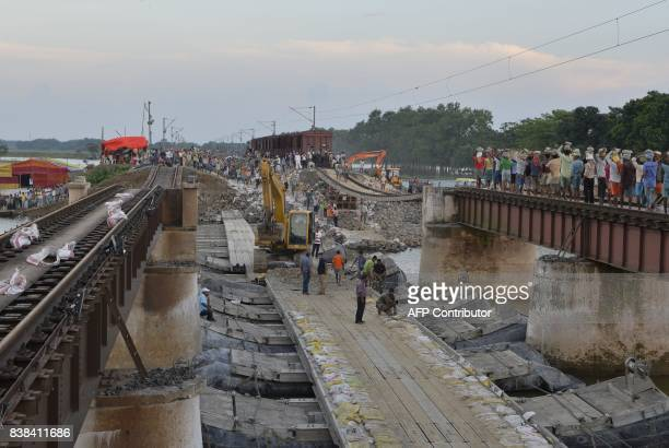 Indian labourers railway staff and army personnel work on a damaged portion of the northeast railway tracks in Ajraill village in Bihar state near...