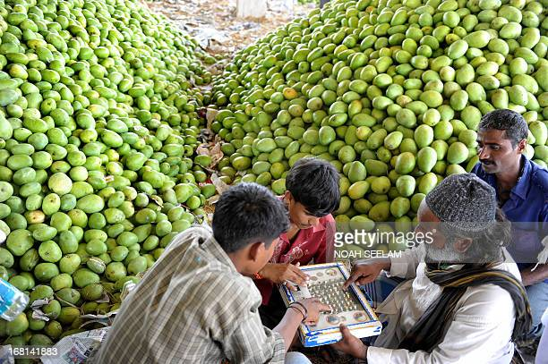Indian labourers select finger rings from a street vendor after unloading mangoes at the Gaddiannaram Fruit Market on the outskirts of Hyderabad on...