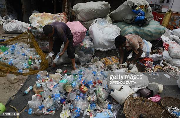 Indian labourers sort plastic bottles after collecting them from ragpickers at a waste items store in Siliguri on June 4 on the eve of World...