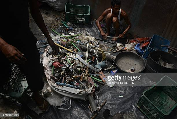 Indian labourers sort recyable items after collecting them from ragpickers at a waste items store in Siliguri on June 4 on the eve of World...