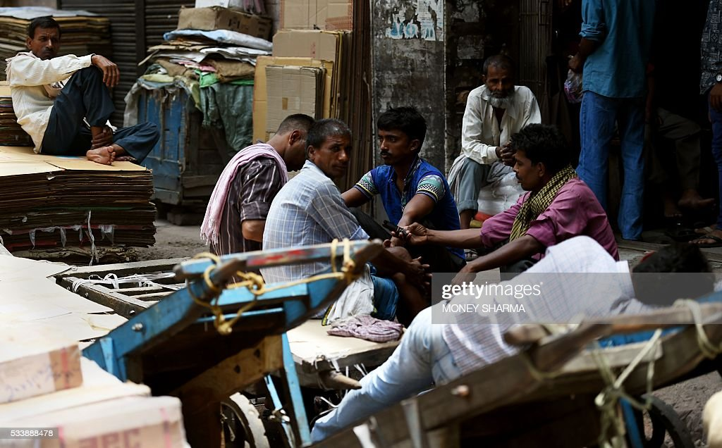 Indian labourers take a break amid rising temperatures in New Delhi on May 24, 2016. / AFP / MONEY