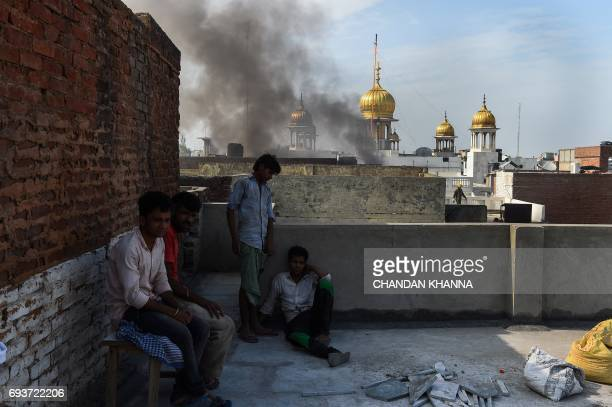 Indian labourers take a break from work as firefighters contain a fire which broke out in Kinari Bazaar in the Chandni Chowk area of New Delhi on...