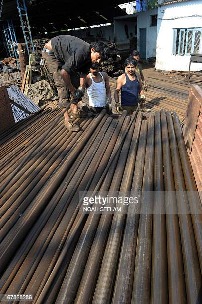 Indian labourers unload metal rods at a factory on the outskirts of Hyderabad on May 1 2013 on Labour Day Labour Day also referred to as May Day...