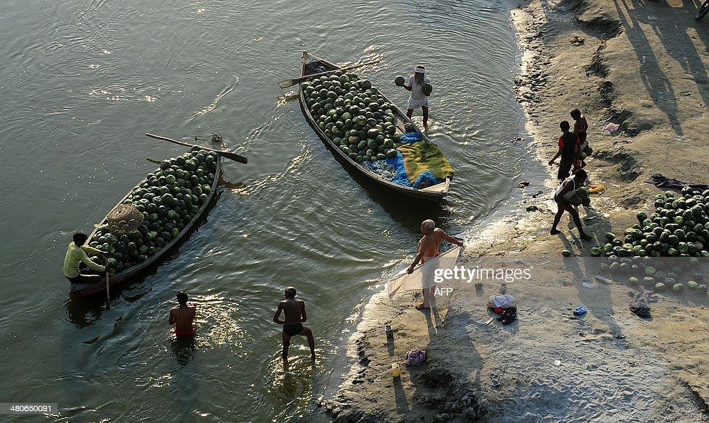 Indian labourers unload pumpkins from a boat in Fafamau village near Allahabad on March 26 2014 AFP PHOTO/SANJAY KANOJIA