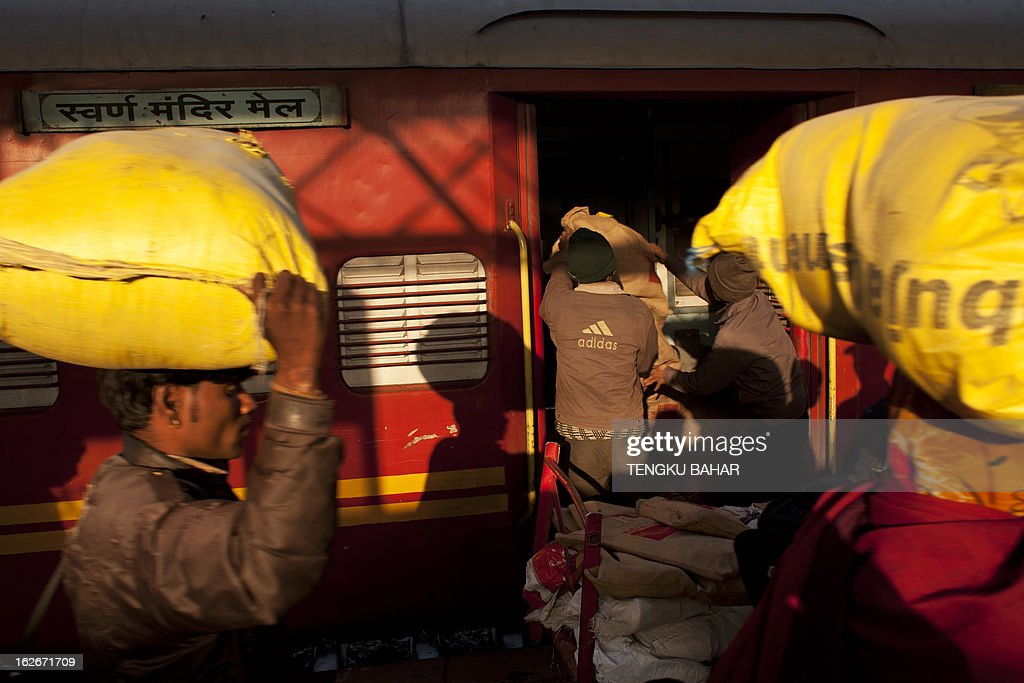 Indian labourers (background) unload sacks containing mail from a specially-designated coach as other labourers (foreground) carry goods following the arrival of a train at the Hazrat Nizamuddin railway station in New Delhi on February 26, 2013, when the railway budget is due to be tabled in Parliament. The railway, the country's largest employer with some 1.4 million people on its payroll, runs 11,000 passenger and freight trains and carries 19 million people daily.