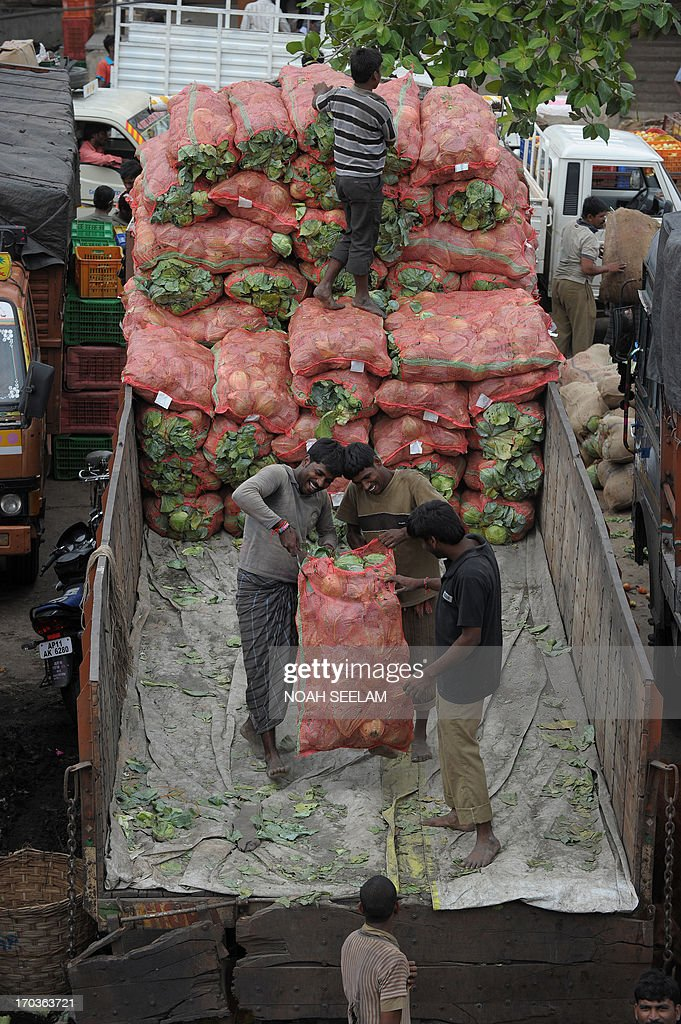 Indian labourers unload sacks of vegetables at a vegetable wholesale market in Hyderabad on June 12, 2013. The National Food Security Bill - 2011, considered to be the world's largest experiment in ensuring food security to the poor, has been a key project of Congress president Sonia Gandhi and finally seems to be getting off the ground at a whopping cost of 1.25 lakh crore Indian rupees. The Bill aims at meeting the food needs of 75% of rural households and 50% of urban households. AFP PHOTO / Noah SEELAM