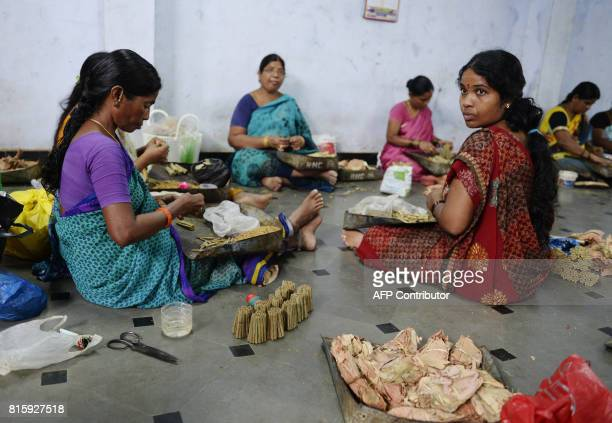 Indian labourers use a combination of chewing tobacco and tendu leaves to make handrolled 'beedi' cigarettes at a workshop in Nizamabad some 167 kms...