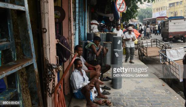 Indian labourers wait for customers in the main wholesale market area of the city in Kolkata on May 31 2017 India's economic growth slowed to 71...