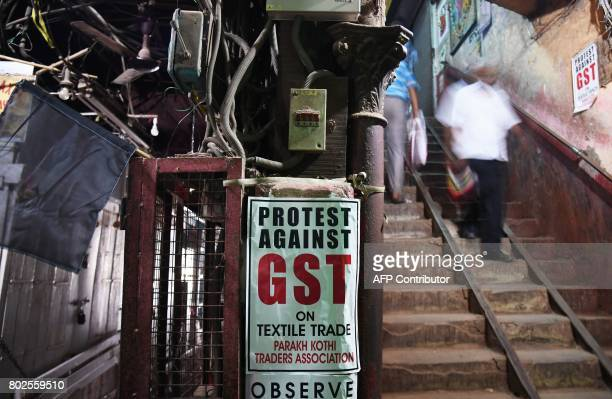 Indian labourers walk past posters protesting against the forthcoming Goods and Services Tax next to textile shops closed in protest in Kolkata on...