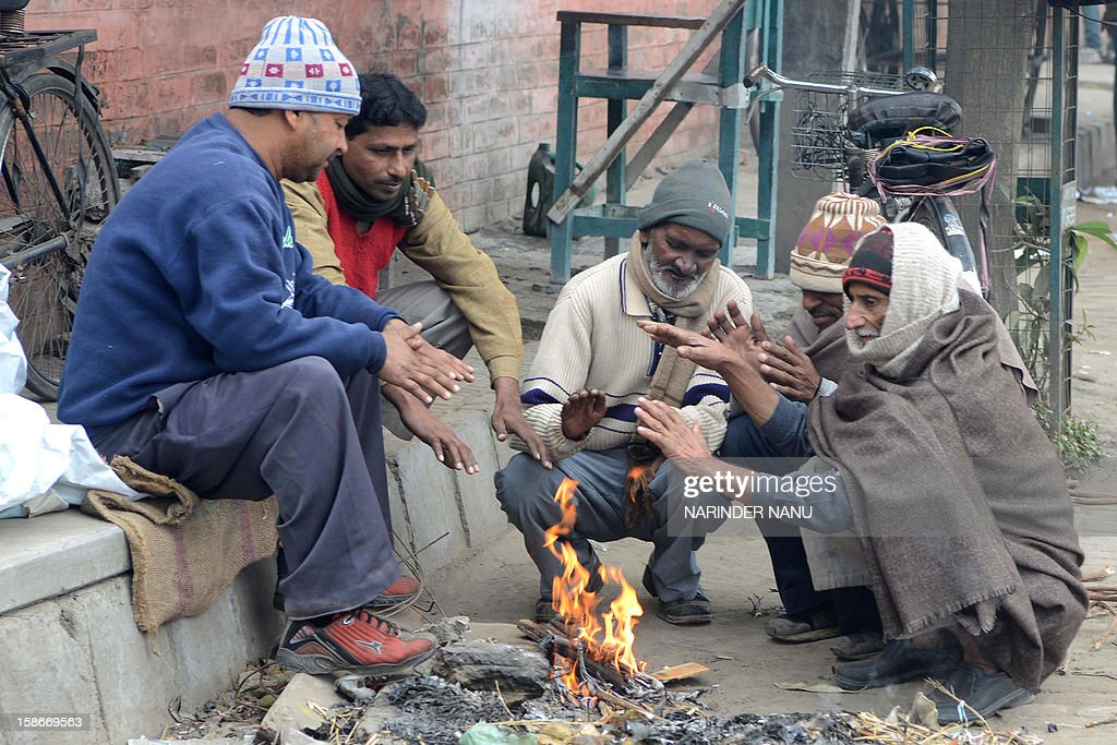Indian labourers warm themselves around a bonfire at a roadside in Amritsar on December 23, 2012. Amritsar in the Punjab region was the coldest area, recording a minimum temperature of 2.4 degree Celsius, two notches below normal.