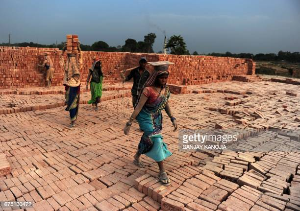 Indian labourers work at a brick factory near Allahabad on April 30 on the eve of International Labour Day / AFP PHOTO / Sanjay KANOJIA