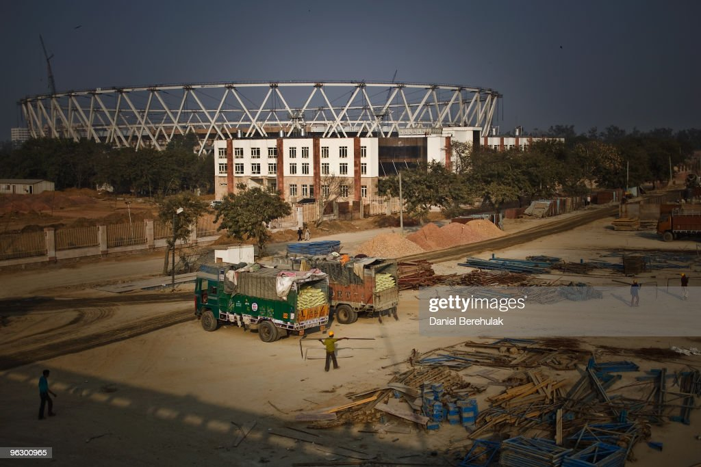 Indian labourers work at a construction project in front of the Jawaharlal Nehru Stadium on January 30, 2010 in New Delhi, India. The Commonwealth Games are due to be held in the Indian capital from October 3-14, 2010, but concerns remain over construction of its sporting and transport infrastructure. The sheer scale of the project has drawn an enormous population of migrant workers from all over India. This week the High Court of Delhi has sought a response from the Government over the alleged failure to provide all the benefits of labour laws to workers involved in construction work for the coming Commonwealth Games. Workers are being paid below the minimum wage in order to complete these projects whilst also being forced to live and work under sub standard conditions.