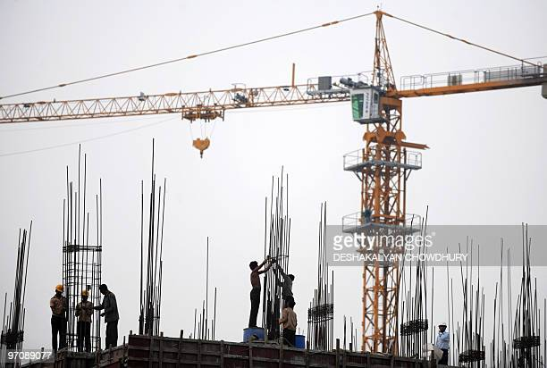 Indian labourers work at a construction site at 'New Town' on the outskirts of Kolkata on February 26 2010 India's economic growth slowed sharply in...