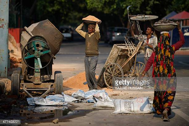 Indian labourers work at a construction site in New Delhi on March 9 2014 India's economy grew by a sluggish 47 percent in the last quarter of 2013...