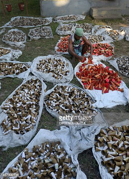 Indian labourers work at a firecracker factory on the outskirts of Siliguri on October 16 2014 Firecrackers are used as a part of celebrations for...