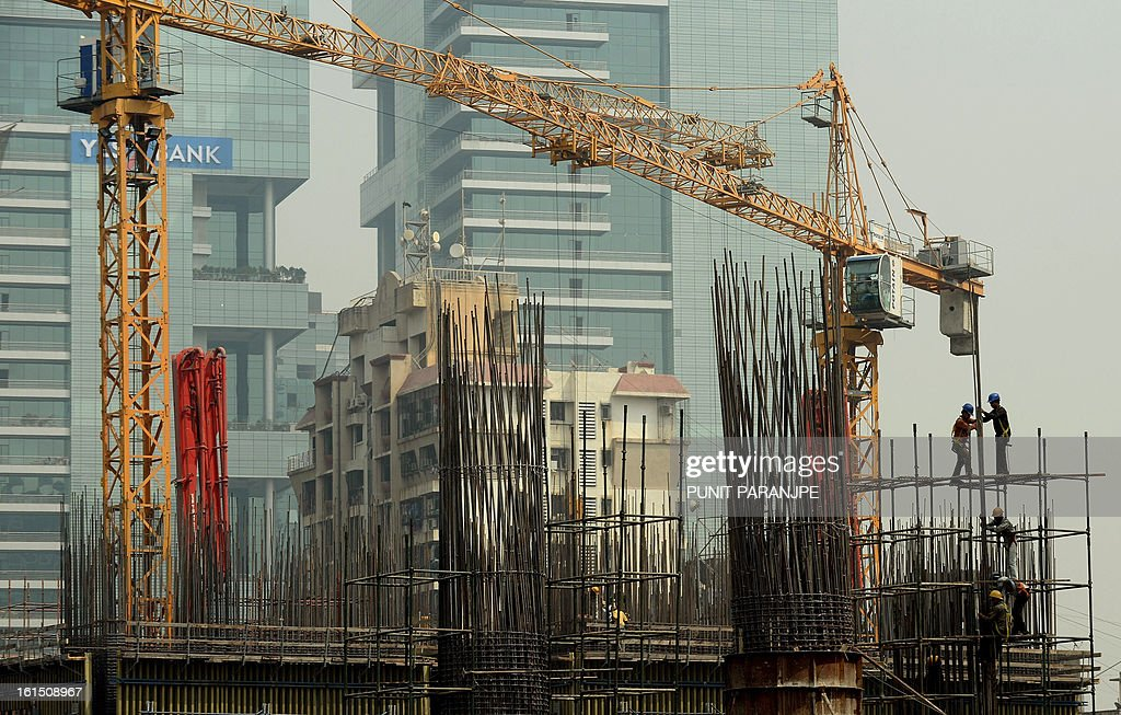 Indian labourers work at the site of a building under construction in Mumbai on February 12, 2013. India's industrial output slipped by a surprise 0.6 percent in December from a year earlier, data showed on February 12, dampening hopes that Asia's third-largest economy could be on the upswing.