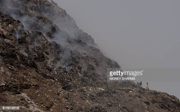 TOPSHOT Indian labourers work near burning trash at a garbage dump in New Delhi on September 27 2016 Nine out of 10 people globally are breathing...