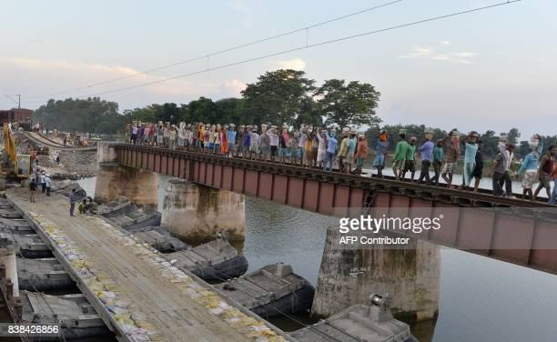 Indian labourers work on a damaged portion of the northeast railway tracks in Ajraill village in Bihar state near Malda on August 24 2017 The death...