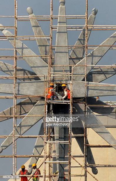 Indian labourers work on a huge 'charkha' or spinning wheelshaped structure at the Mahatma Mandir in Gandhinagar some 30 kms from Ahmedabad on...