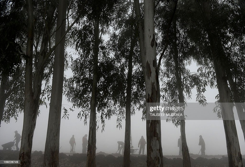 Indian labourers work on a road during a dense fog along the India-Pakistan border in Suchit-Garh, 36 kms southwest of Jammu on January 10, 2013. The beheading of an Indian soldier may have sparked a war of words between Delhi and Islamabad but the two nuclear rivals are both determined to prevent it from wrecking a fragile peace process. Two Indian soldiers died after a firefight erupted in disputed Kashmir on Tuesday as a patrol moving in fog discovered Pakistani troops about 500 metres (yards) inside Indian territory, according to the Indian army. AFP PHOTO/Tauseef MUSTAFA