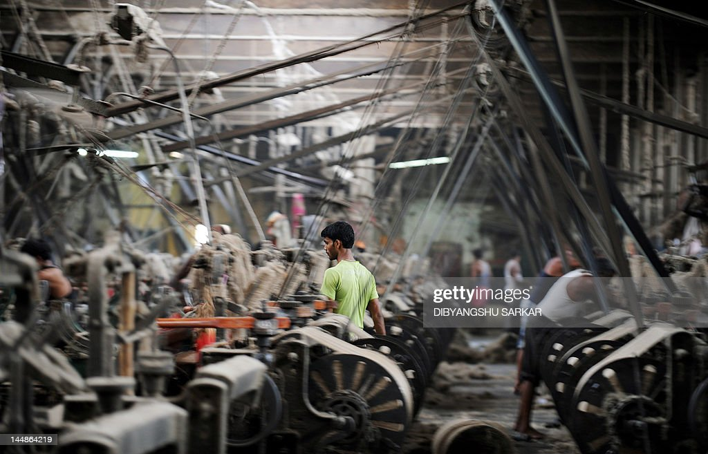 Indian labourers work on machines inside a jute mill at Jagatdal some 75kms north of Kolkata on May 14, 2012. Jute is a crop which relies heavily on rainfall and cultivation is chiefly concentrated in South Asia, it is the cheapest vegetable fibre procured from the bast or skin of the plant's stem and the second most important vegetable fibre after cotton, in terms of usage, global consumption, production, and availability. It has high tensile strength, low extensibility, and ensures better breathability of fabrics. Jute fibre is 100% bio-degradable and recyclable and thus environmentally friendly. The British East India Company was the first jute trader in South Asia and established links with European countries notably Dundee in Scotland which gave rise to 'The Jute Barons' who eventually set up mills on the outskirts of Kolkata. In the 21st century jute has a variety of uses such as grain bags, home textiles, floor coverings and even footwear in the form of espadrilles. AFP PHOTO/ Dibyangshu SARKAR