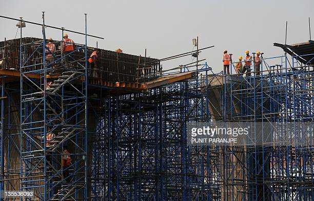 Indian labourers work on the construction site near the international airport in Mumbai on December 12 2011 India's industrial output shrank 51...
