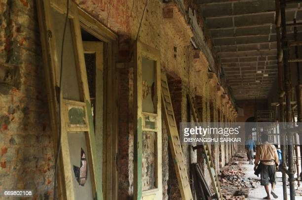 Indian labourers work on the renovation of the historic Writers' Building in Kolkata on World Heritage Day on April 18 2017 The redbrick complex...
