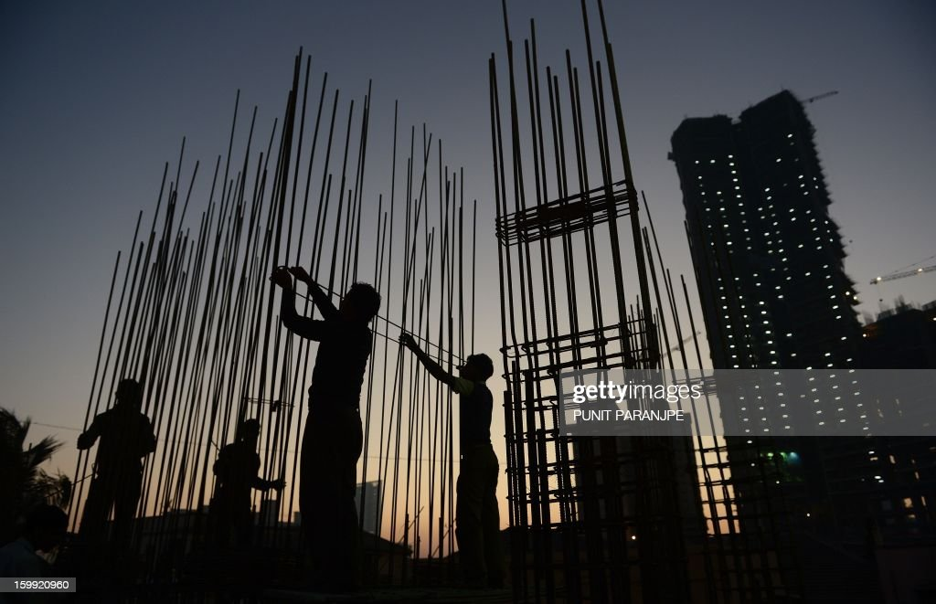 Indian labourers work on the site of an under-construction building in Mumbai on January 23, 2013. India is experiencing galloping urbanisation, part of a global trend that has led more than half of the world's population to reside in towns and cities.