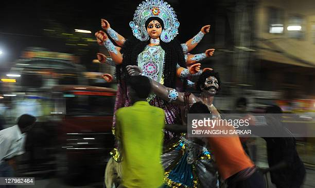 Indian labours carry a finished clay statue of Hindu goddess Durga out of the workshop to take it to the place of worship in Kumartoli the idol...