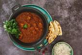 Indian lamb Rogan Josh with traditional naan bread and rice. Top view, blank space, dark toned image