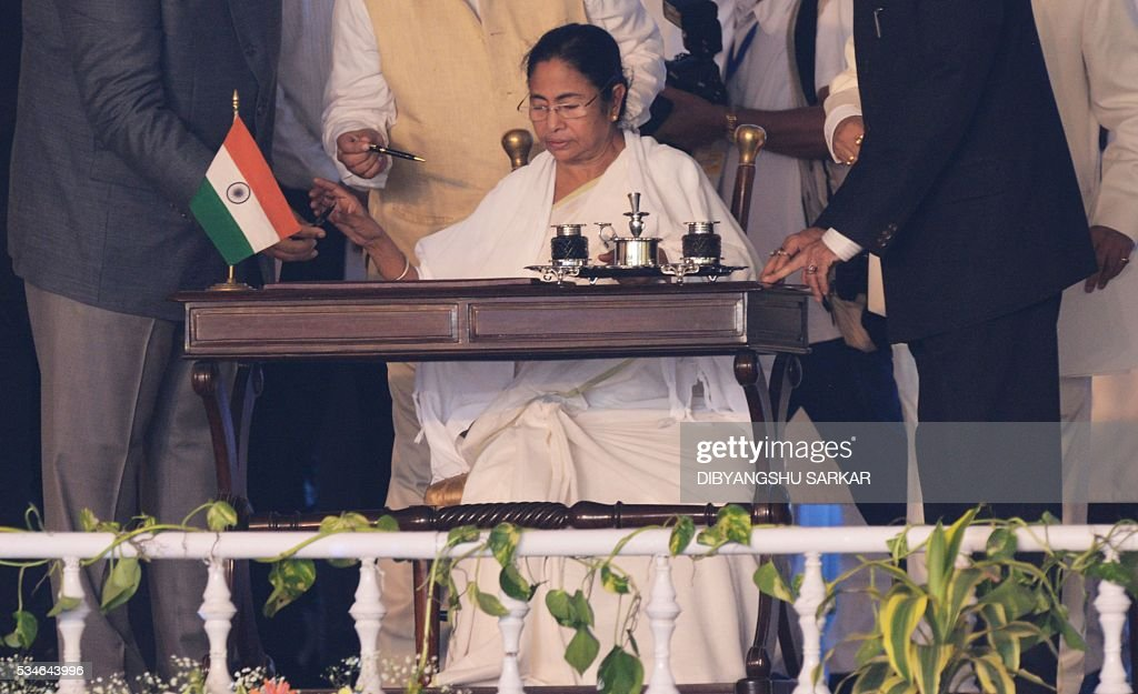 Indian leader of the All India Trinamool Congress (AITMC) Mamata Banerjee signs papers during her swearing-in ceremony as chief minister of the eastern Indian state of West Bengal in Kolkata on May 27, 2016. / AFP / Dibyangshu SARKAR