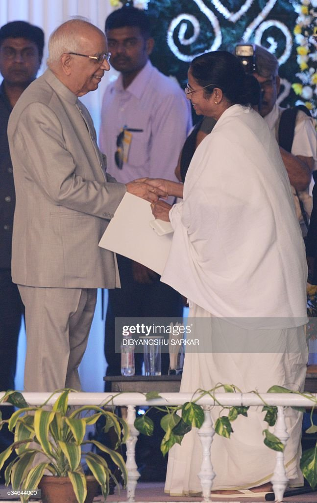 Indian leader of the All India Trinamool Congress (AITMC) Mamata Banerjee (R) shakes hands with governer Keshari Nath Tripathi during her swearing-in ceremony as chief minister of the eastern Indian state of West Bengal in Kolkata on May 27, 2016. / AFP / Dibyangshu SARKAR