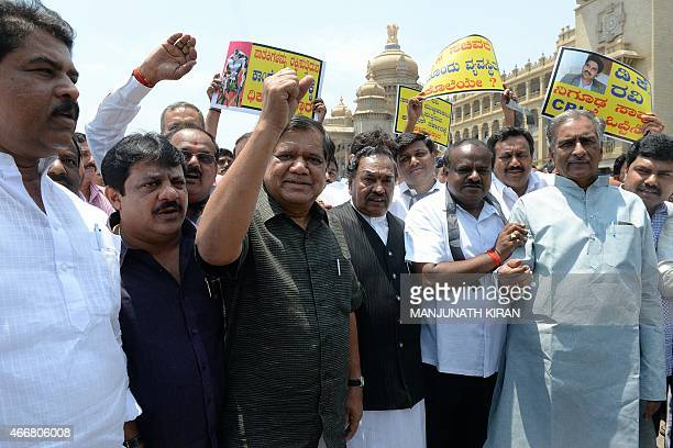 Indian leaders and members of the opposition in the Karnataka State Legislative Assembly shout slogans and stage a protest outside the Vidhana Soudha...