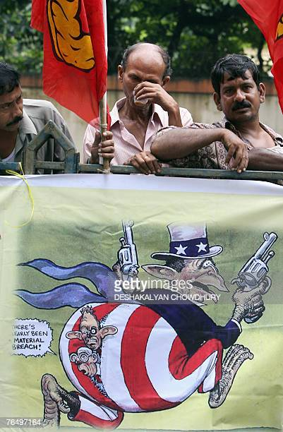 Indian Left activists hold flags as they stand behind an antiUS banner during a flag off ceremony for a 'Jatha' in Kolkata 04 September 2007 against...