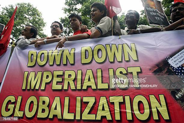 Indian Left activists hold posters as they stand behind an antiUS banner during a flag off ceremony for a 'Jatha' in Kolkata 04 September 2007...