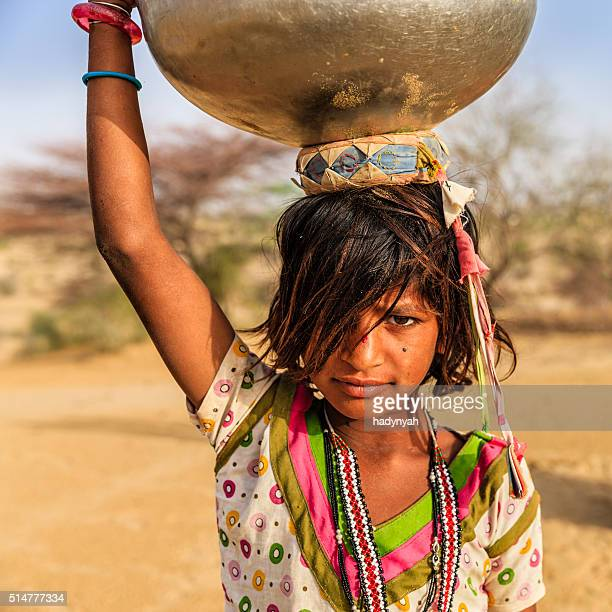 Indian little girl carrying on her head water from well