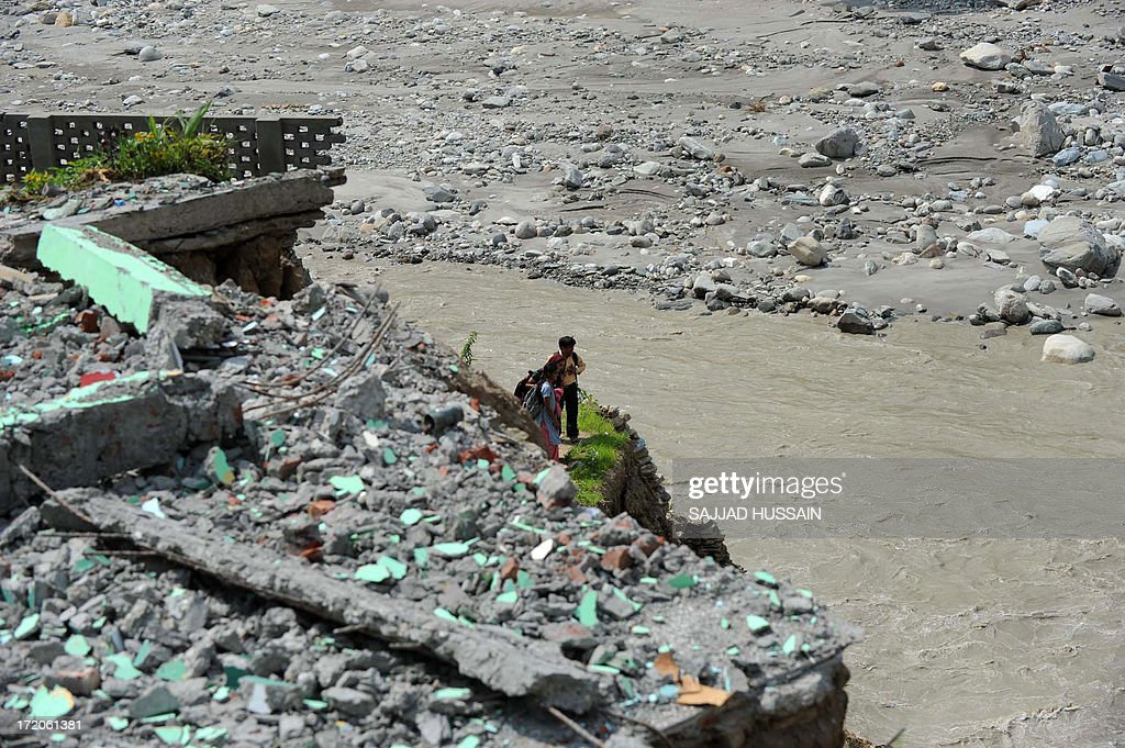 Indian locals look at the damaged road alongside the Mandakini river at Silli, in the flood affected area of northern Uttarakhand state on July 1, 2013. Construction along river banks will be banned in a devastated north Indian state amid concerns unchecked development fuelled last month's flash floods and landslides that killed thousands, the state's top official said July 1.