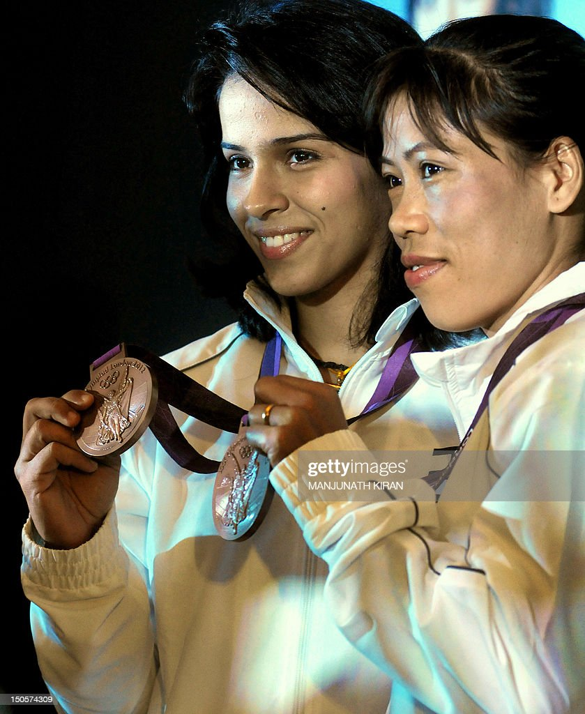 Indian London Olympic 2012 medalists for badminton Saina Nehwal (L) and boxing, Mary Kom display their bronze medals during a felicitation function organised by a global nutrition company in Bangalore on August 22, 2012. Two silver and four bronze Olympic medals were brought home by Indian athletes after the 2012 Games held in London. AFP PHOTO/Manjunath KIRAN