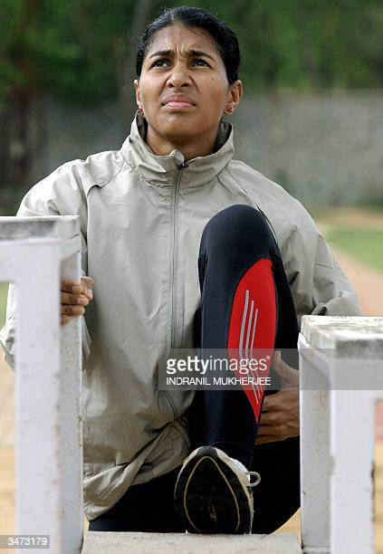 Indian long jumper Anju Bobby George performs warm up exercises at the Sports Authority of India campus in Bangalore 27 April 2004 as she trains for...
