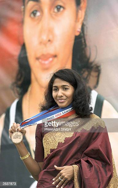 Indian long Jumper Anju George displays her bronze medal as she stands in front of her portrait during a felicitation ceremony at Jawahar lal Nehru...
