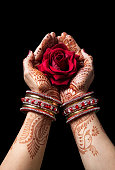 Woman hands with henna holding red rose isolated on black background with clipping path