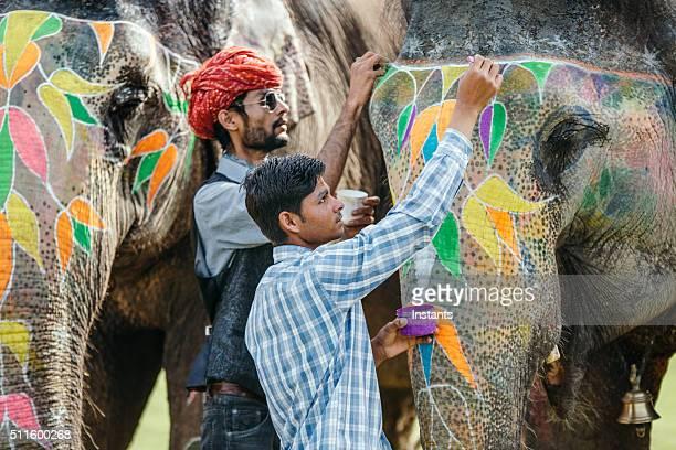 Indian mahouts decorating elephants