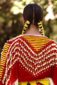 A young American Indian girl in colorful traditional costume with braided hair at a pow wow in Hawaii.  Ribbons and shells adorn her braided hair and patterned clothing. A vertical close-up color phot
