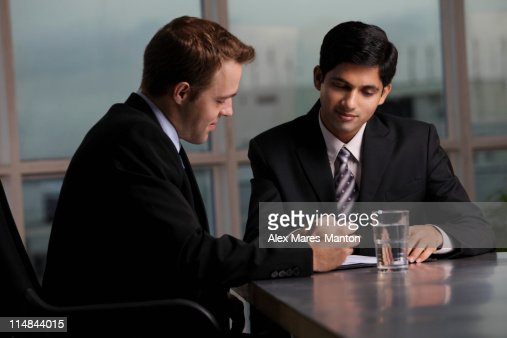 Indian man and Caucasian men discussing a document