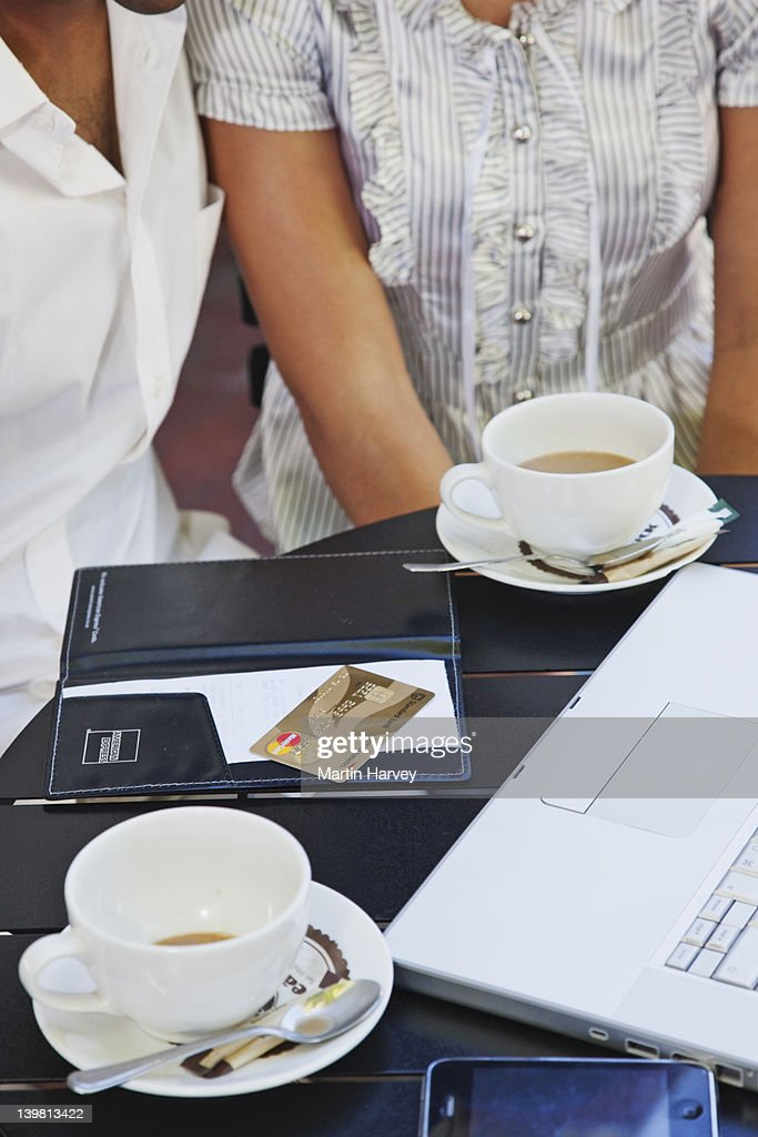 Indian man and woman (25, 24 years old) at coffee shop paying the bill, Close-up, Simons Town, Cape Town, Western Cape Province, South Africa : Stock Photo