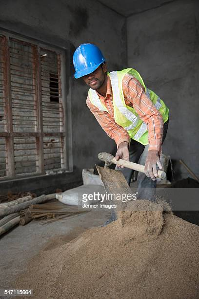 Indian man, construction worker mixing cement