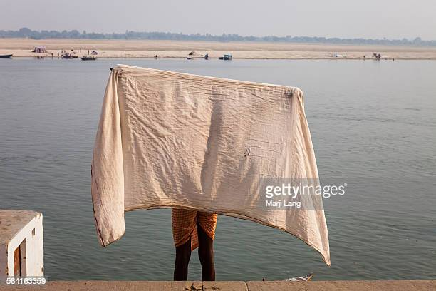 Indian man drying his dhoti by the Ganges river