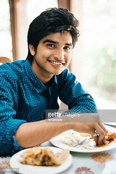 Indian man eating with hands in Indian Restaurant